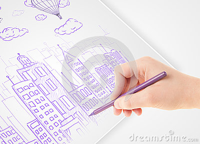A person drawing sketch of a city with balloons and clouds on a Stock Photo
