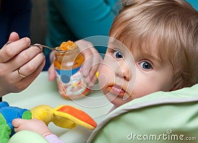 Person feeding baby girl