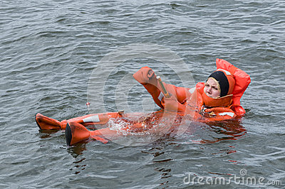 Person floating in survival suit lights handflare Editorial Photo
