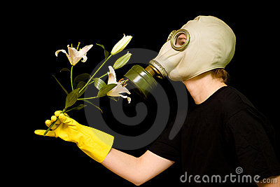 Person in a gas mask smells a flower