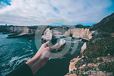 Person Holding Smartphone Capturing Pictures Of Body Of Water Beside Rock Formations Under Cloudy Sky During Daytime Free Public Domain Cc0 Image