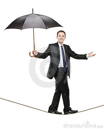 A person holding an umbrella and walking on a rope