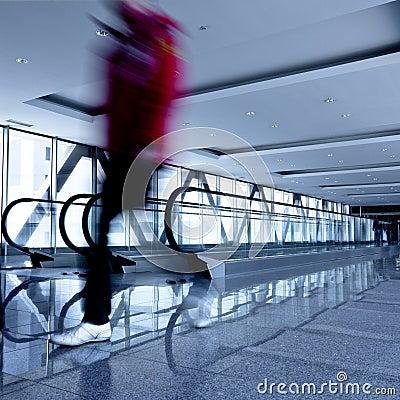 Person move in grey corridor with escalators