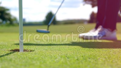 Person plays golf, putting a ball into a hole. 4K stock video footage
