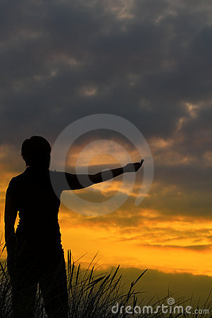 Person pointing at sunset