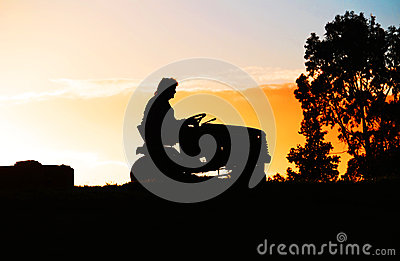 Person on a Ride On Lawn Mower on Farm at Sundown