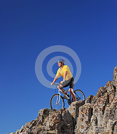 Person riding a bike on rocks against blue sky