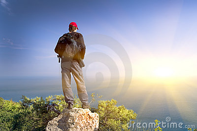 The person on a rock looks  at ocean