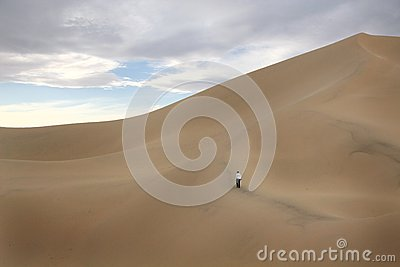 Person Walking on Large Sand Dune Editorial Image