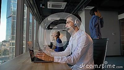 Persona atractiva del negocio en centro de atención telefónica de la oficina que habla con el cliente y entonces la sonrisa con l almacen de metraje de vídeo