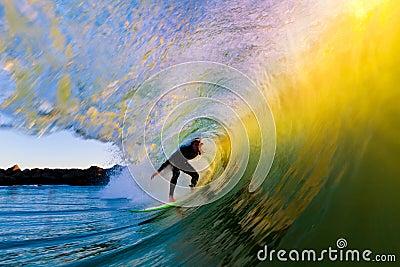 Persona que practica surf en onda en la puesta del sol