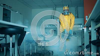 Persona saniza sala de laboratorio con un pulverizador almacen de metraje de vídeo