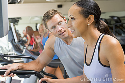 Personal Trainer Encouraging Woman Using Treadmill
