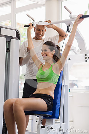 Personal trainer helping woman in wellness club