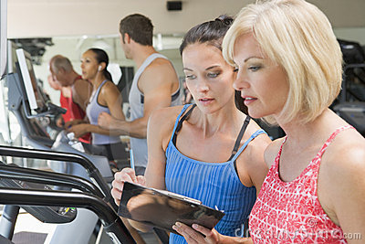 Personal Trainer Instructing Woman On Treadmill