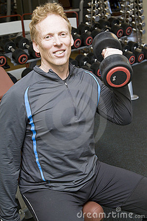 Personal trainer lifting weights in a modern gym