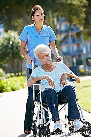 Personale che dispensa le cure che spinge donna maggiore infelice in sedia a rotelle
