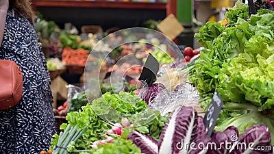 Personas navegando en un puesto de frutas y verduras en el Borough Market, Londres almacen de video