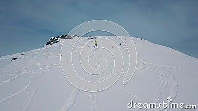Personne sportive en matériel de snowboard ou de ski au sommet d'une montagne enneigée banque de vidéos