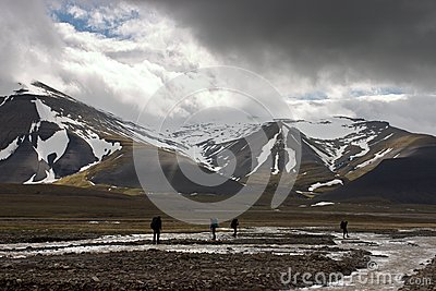 Persons traveling across arctic tundra