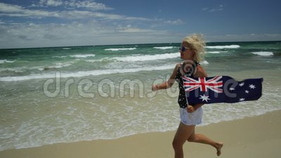 Perth beaches enjoying. Close up of woman running on white beach waving Australian Flag. Blonde lifestyle tourist enjoying in Mettams Pool, North Beach near stock footage
