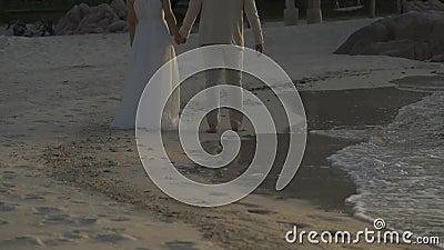 Perto do corpo, Bride e Groom estão segurando e caminhando na praia ao lado do mar e acenando no tempo do Crepúsculo video estoque