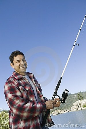 Pesca di mosca dell uomo sul lago