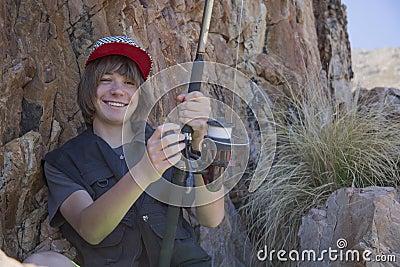 Pesca joven del adolescente por el mar