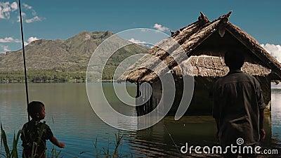 Pesca locale del ragazzino e del pescatore sul lago Batur vicino ad una piccola capanna, editoriale archivi video