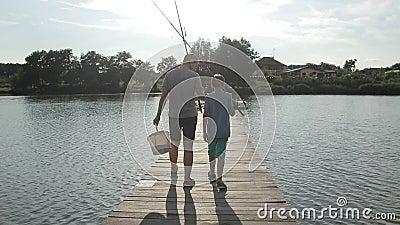 Pesca que va del padre y del hijo con las barras en el lago almacen de metraje de vídeo
