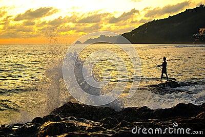 Pescador com a onda grande do respingo