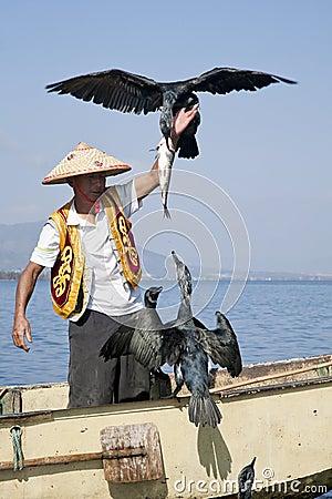 Pescador con el pájaro y los pescados Fotografía editorial