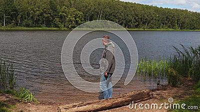 Pescador divertido en el lago almacen de metraje de vídeo