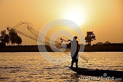 Pescador en la puesta del sol