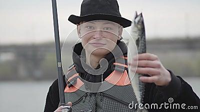 Pescador feliz seguro novo bonito de Portait que veste um tampão com uma borda no fand da captura do amanhecer que mostra peixes vídeos de arquivo