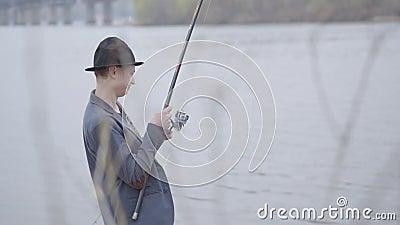 Pescador novo em um revestimento e em um tampão com uma borda nos peixes do scomber da captura do amanhecer com gerencio no rio p vídeos de arquivo