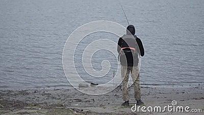 Pescador seguro novo em calças caqui nos peixes de travamento do amanhecer no gerencio no rio perto da cidade vídeos de arquivo