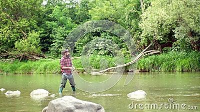 pescados en el gancho de leva Hombre con las cañas de pescar en litera del río angler La pesca con mosca es la más renombrada com almacen de metraje de vídeo