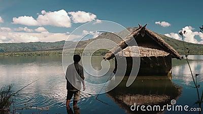 Pesce di cattura dell'uomo locale di balinese con i coni retinici sul lago Batur vicino ad una piccola capanna archivi video