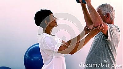 Pesos de levantamento da mão do homem idoso com fisioterapeuta video estoque