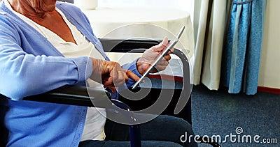 Pessoa aposentada na cadeira de roda usando o tablet pc vídeos de arquivo