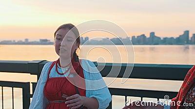 Pessoas de fantasias populares russos paradas na beira-mar durante o pôr do sol e cantando uma canção video estoque
