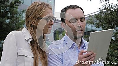Pessoas de negócios se encontrando fora do tablet eletrônico video estoque
