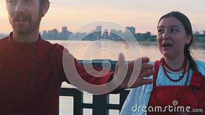 Pessoas em fantasias populares russas que pararam na beira-mar durante o pôr do sol e cantaram uma canção - edifícios modernos em filme