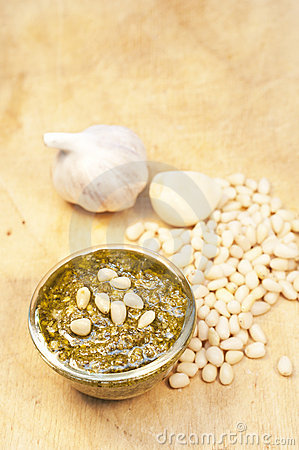 Pesto, garlic and cedar nuts on wooden background