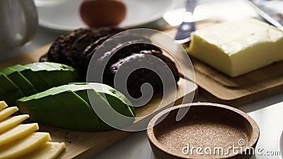 Petit déjeuner parfait Petit déjeuner le matin avec fromage, avocat, beurre, pain brun, oeuf La main de la fille met une tasse ou banque de vidéos