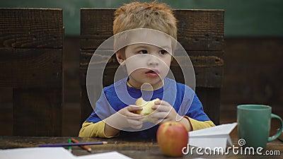 Petit garçon blond et mou assis dans une chaise en bois et mangeant de gros fruits à la pomme rouge. Portrait sur fond flou, clo banque de vidéos