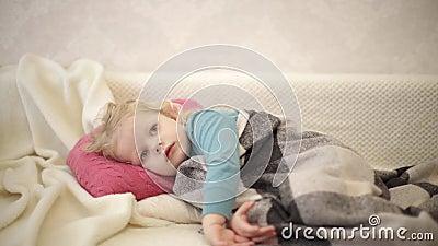 Petit mignon garçon drôle de 3 ans, blond est allongé sur un canapé sous un plaid et regarde des dessins animés à la télévision clips vidéos