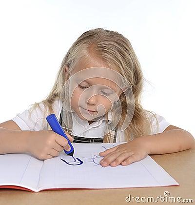 petit schoogirl mignon heureux sur le dessin de bureau sur le bloc notes avec le marqueur photo. Black Bedroom Furniture Sets. Home Design Ideas