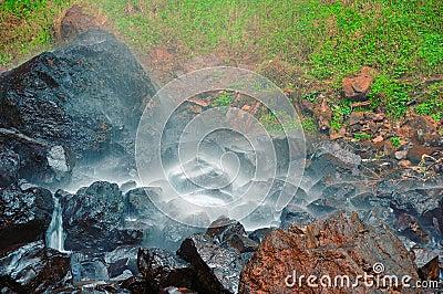Petite cascade à écriture ligne par ligne sur les roches humides
